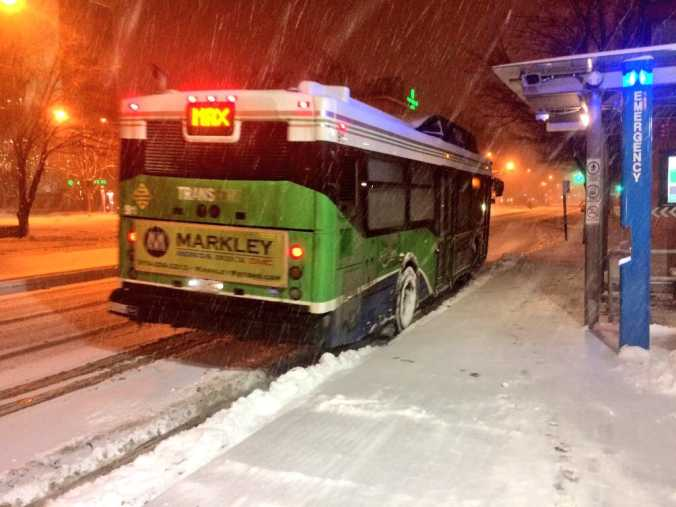 A Transfort bus in the snow.